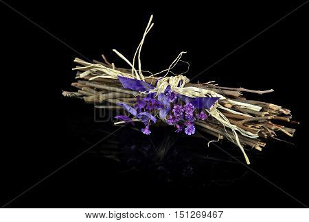 purple violet bouquet with satin ribbon tied around twig bundle on black reflection