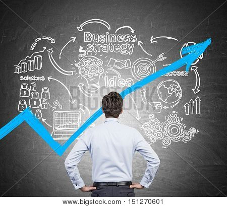 Rear view of man looking at startup sketch and blue growing graph on blackboard. Concept of analysis.