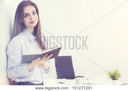 Businesswoman With Notepad In Sunlit Office