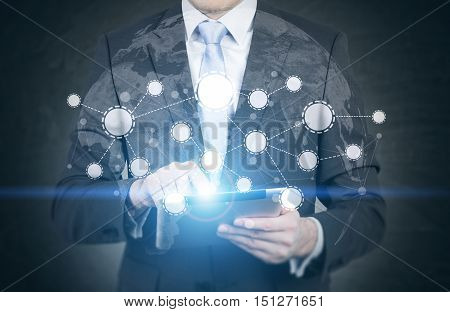 Close up of businessman working with his tablet. Network and world map are in the foreground. Concept of globalisation.