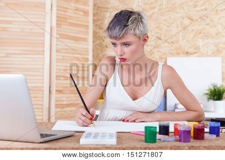 Centered woman is looking at laptop screen and copying an image she is seeing. Concept of art forgery.