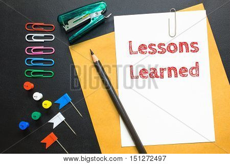 Text Lessons learned on white paper background / business concept