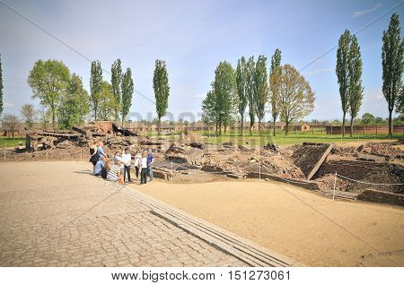 OSWIECIM POLAND - MAY 12 2016: Tourists visiting the concentration camp Auschwitz Birkenau II in Brzezinka Poland.