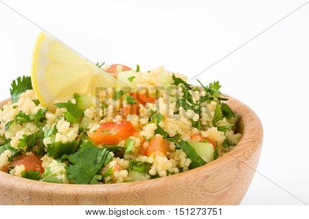 Tabbouleh salad with couscous and vegetables in bowl isolated