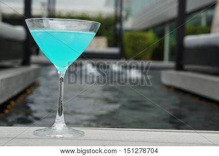 blue kamikaze cocktail with pool view  background -soft focus