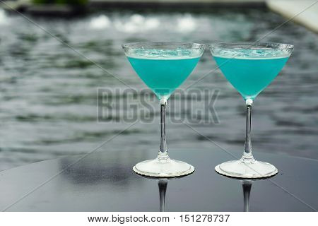 blue kamikaze cocktail with pool view as background - soft and select focus