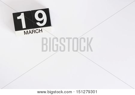 March 19th. Day 19 of month, wooden color calendar with flower on white background. Spring time. Earth Hour and International client's Days.