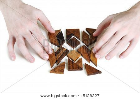 Closeup Of Mans Hands Assembling Wooden Square Puzzle, Isolated