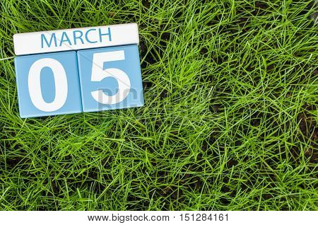 March 5th. Day 5 of month, wooden color calendar on football green grass background. Spring time, empty space for text.