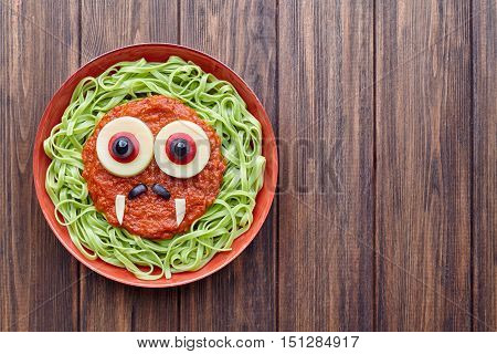 Green spaghetti pasta scary halloween food vampire monster with smile, fake blood tomato sauce moustaches and funny big mozzarella eyeballs decoration kid party meal on vintage table
