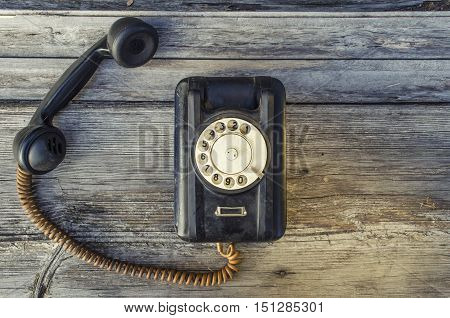 Old battered black telephone on a wooden texture