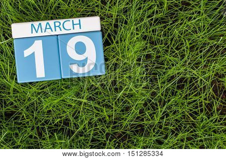 March 19th. Day 19 of month, calendar with football green grass background. Spring time. Earth Hour and International client's Days.