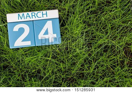 March 24th. Day 24 of month, calendar on football green grass background. Spring time, empty space for text.