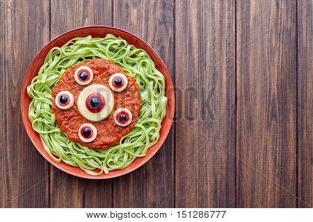 Green spaghetti creative pasta scary halloween party food monster meal with fake blood tomato sauce and many red mozzarella eyeballs decoration celebration kid party meal on vintage table.