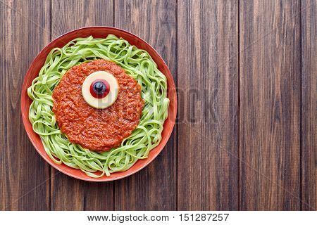 Green spaghetti creative pasta halloween party food cyclopes monster meal with fake blood tomato sauce and red eyeball decoration celebration kid party meal on vintage table.