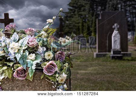 Flowers on a headstones in a cemetery bokeh effect in background.