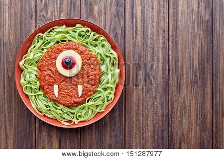 Green spaghetti creative pasta halloween food cyclopes monster meal with fake blood tomato sauce and mozzarella eyeball decoration celebration kid party meal on vintage table.