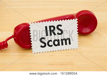 Getting a call that is an IRS Scam A retro red phone with note card on a desk with text IRS Scam