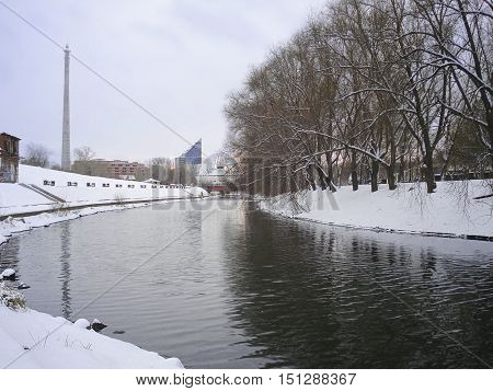 Winter cityscape with not frozen Iset River. Yekaterinburg. December. Trees are reflected in water. On a background buildings of circus the unfinished house and a television tower are visible. In Yekaterinburg in 2018 will pass the soccer World Cup