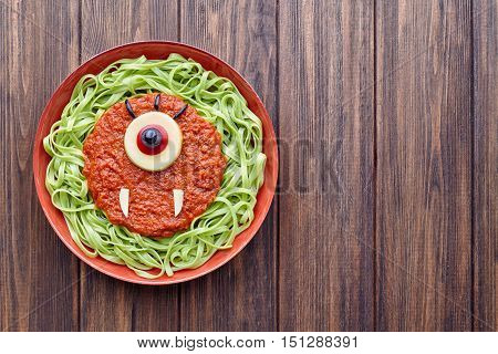Green spaghetti creative pasta halloween food cyclopes vampire monster meal with fake blood tomato sauce and mozzarella eyeball decoration celebration kid party meal on vintage table.