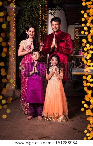 cheerful indian family welcoming on diwali night outside home with diwali lighting, indian couple and kids or people in namaskar pose welcoming guests on diwali celebration or festival night