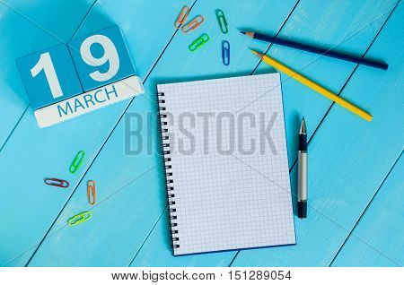 March 19th. Day 19 of month, calendar on blue wooden table background with notepad. Spring time. Earth Hour and International client's Days.