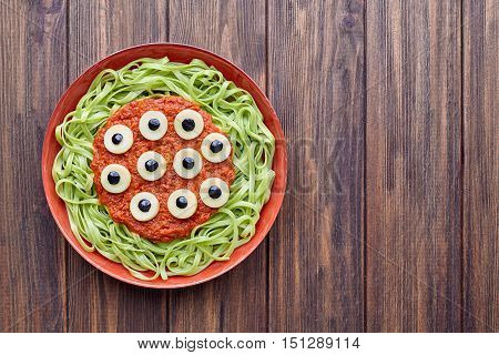 Green spaghetti creative pasta scary halloween party food monster meal with fake blood tomato sauce and many mozzarella eyeballs terrifying decoration celebration kid party meal on vintage table.