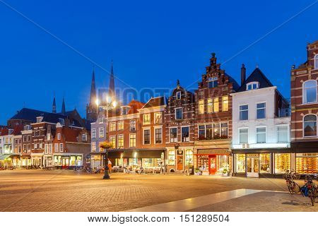 The central market square and colorful facades of the old buildings in the city Delft on sunset. Netherlands.