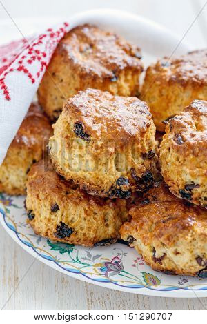 Homemade scones with dried berries on a white wooden table.