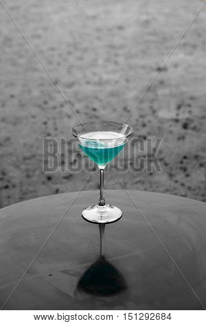 blue kamikaze cocktail with pool view during raining - dramatic with soft and select focus