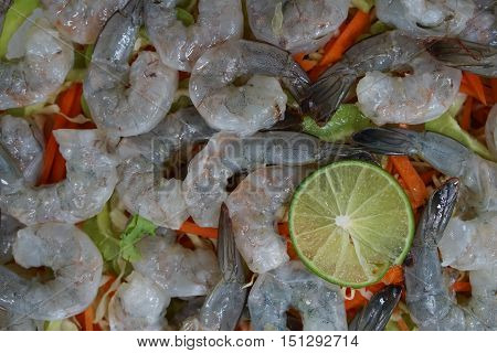 raw fresh shrimp prepared arrange on chopped vegetable with a slice of lime