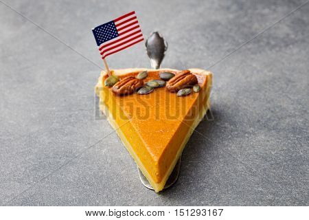Pumpkin pie, tart made for Thanksgiving day with American flag on top. Grey stone background.