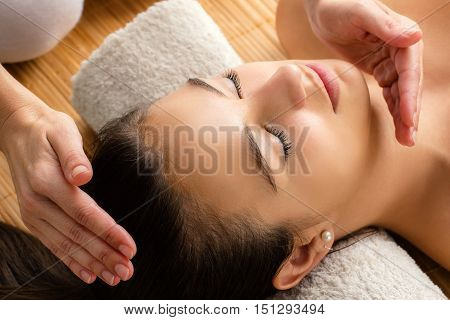 Close up portrait of attractive woman at reiki session. Therapist healing with hands next to head.