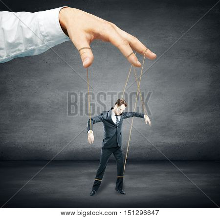 Hand controlling businessman as puppet on dark concrete background. Control concept