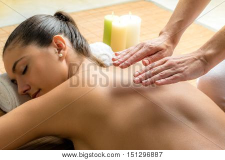 Close up portrait of attractive woman receiving alternative therapy on spine.Therapist working on energy channels on woman's back.