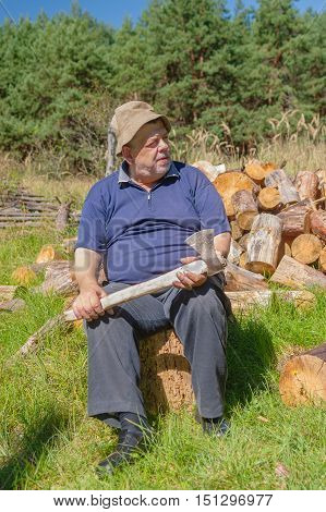 Senior man sitting on a log getting ready to chop pile of firewoods for winter kindling