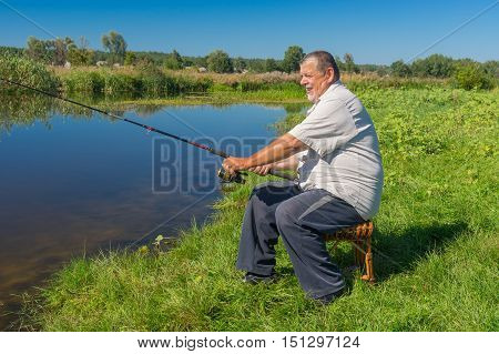 Senior fisherman sitting on a wicker stool with spinning rod and ready to catch fish in small river Merla in central Ukraine
