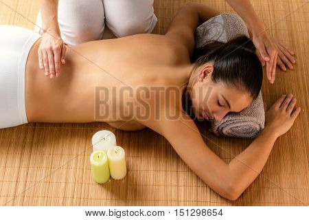 Top view of attractive woman at alternative treatment session. Reiki therapist working on energy channels on woman's spine.