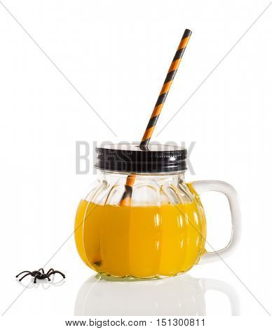 Halloween drink served in pumpkin shaped glass with drinking straw