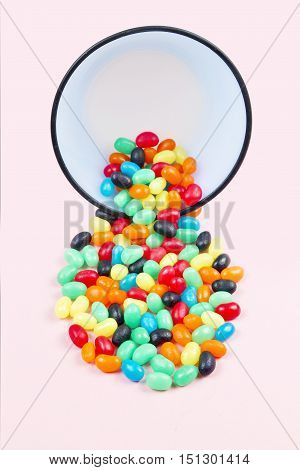 Brightly colored jelly candy being poured out of a bowl on a soft pastel pink background