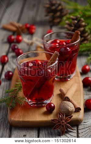 Cranberry drink on wooden background with fir branches and fresh berries, selective focus
