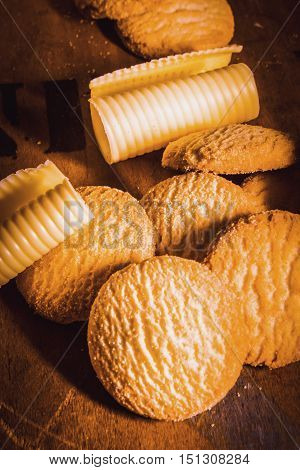 Rich buttery shortbread rounds biscuits or cookies in a heap on a wood table with neat coils of fresh farm butter