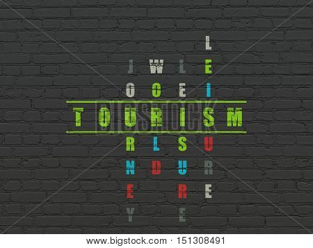 Vacation concept: Painted green word Tourism in solving Crossword Puzzle