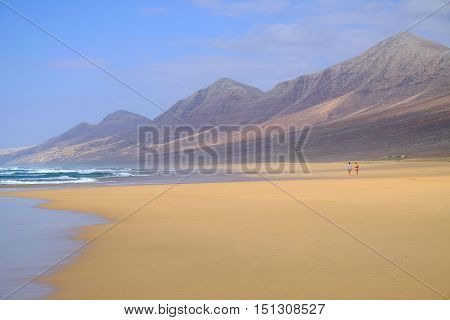 Wonderful view on the beach Cofete with couple walking along it. Location the Canary Island Fuerteventura Spain.