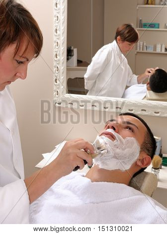 Shaving at the barber of a young boy in retro style with razor and shaving soap