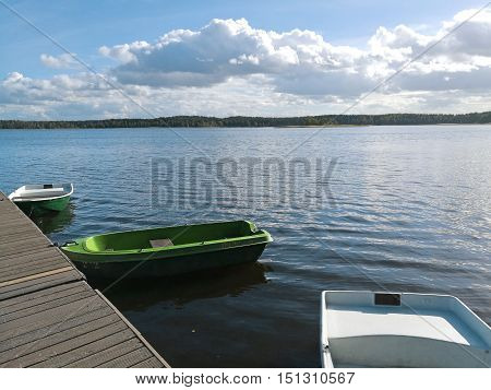 Empty lonely boat on autumn blue lake.