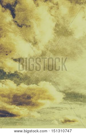 Old cloud texture with towering white cumulus formations in the yellow heavens above. Vintage background