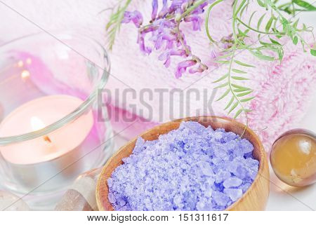 Spa setting with lilac flowers bath salts and a candle