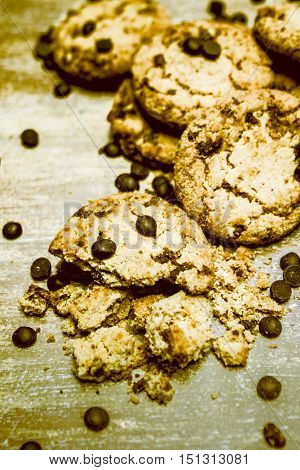 Still Life Photo on a Pile of Broken and Whole Fresh Baked Crispy Chocolate Chip Cookies Arranged on Wooden Table Surface Surrounded by Chocolate Chips