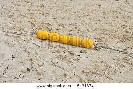 Four Yellow Marker Buoys On Sand Beach